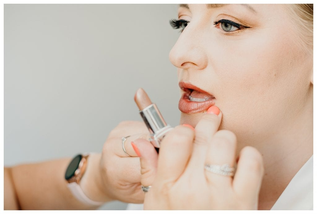 close up makeup artist putting lipstick on bride before her Bern Switzerland wedding
