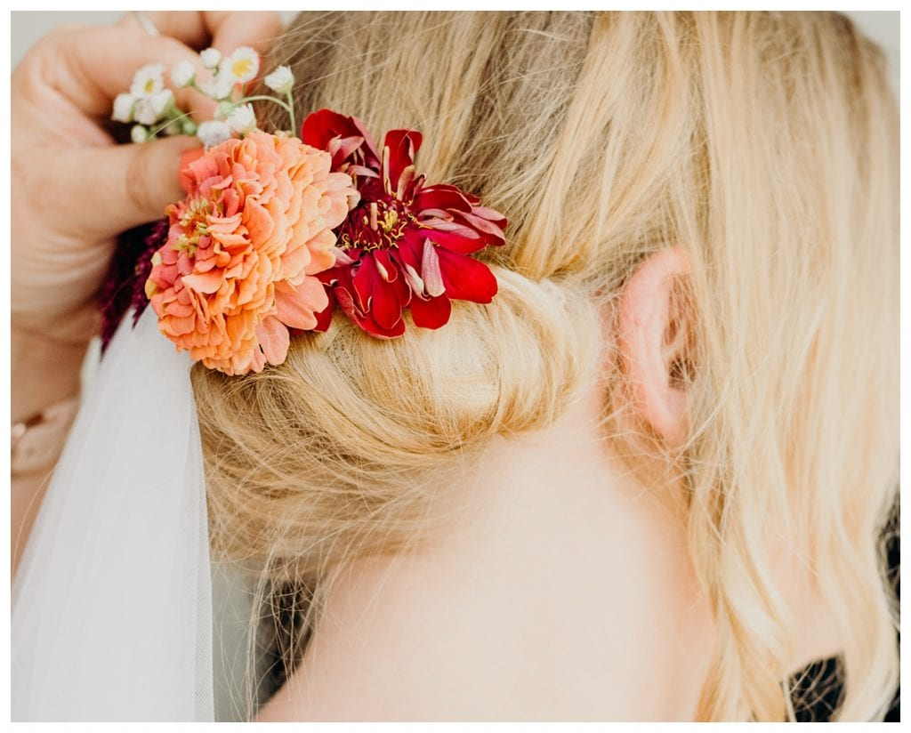 closeup of pink and orange flowers in bride's bun in Bern Switzerland