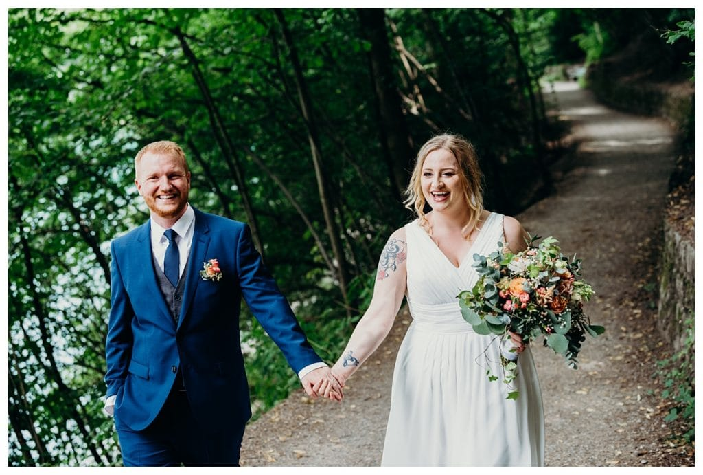 bride and groom laughing holding hands in a Bern Switzerland forest