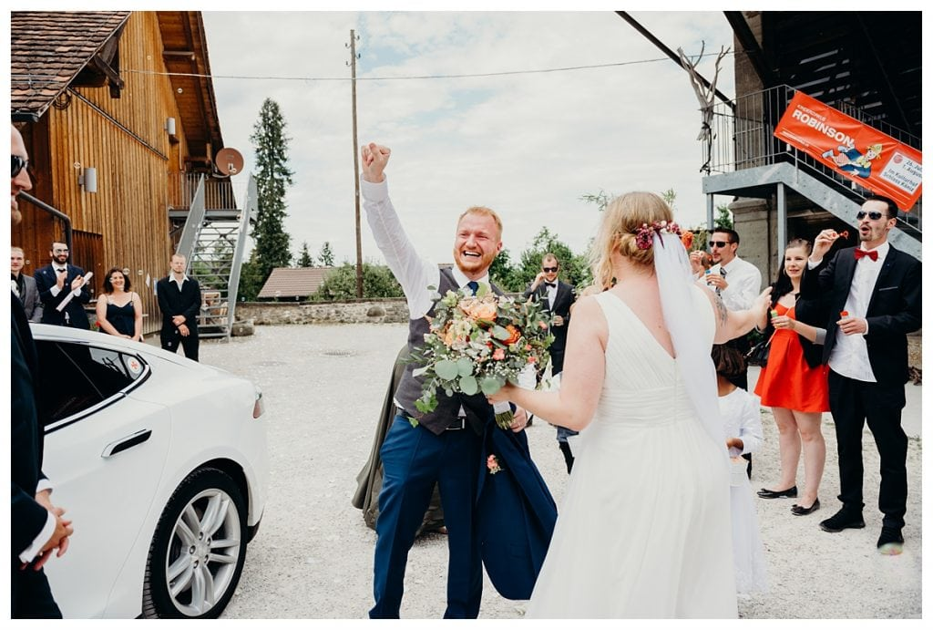groom raising fist during grand entrance at koniz castle in Bern Switzerland