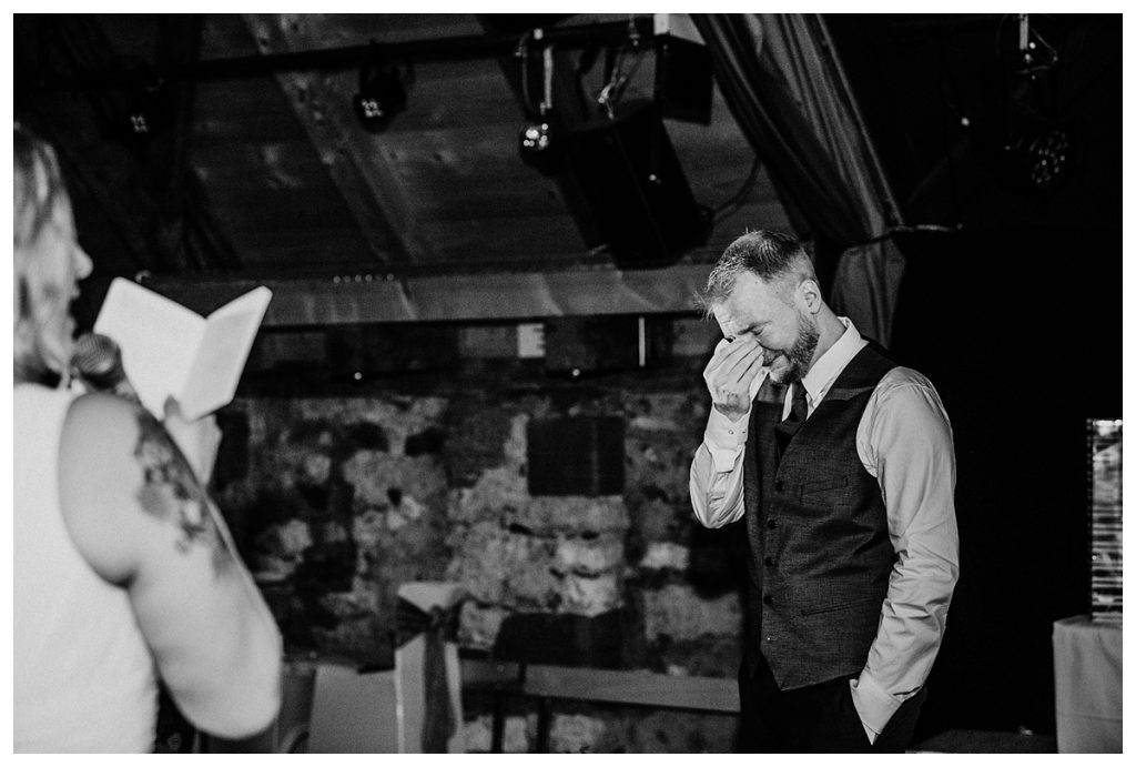 groom wiping tears as bride reads vows during their koniz castle wedding reception in Bern Switzerland