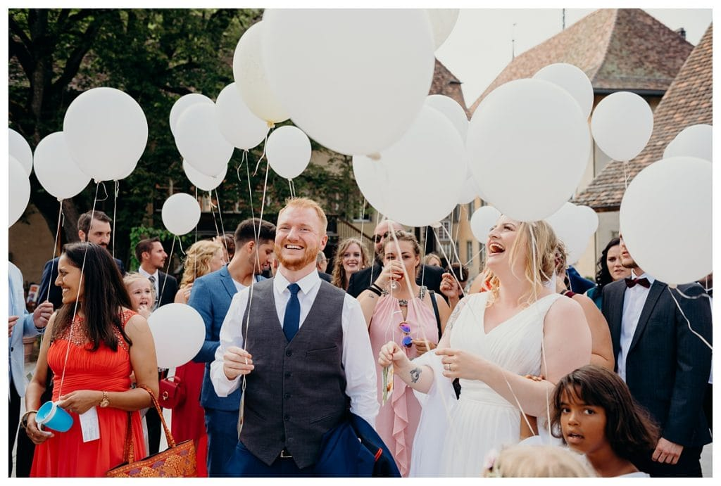 bride, groom, and guests smiling holding white balloons at Kulturhof Schloss Köniz in Bern Switzerland