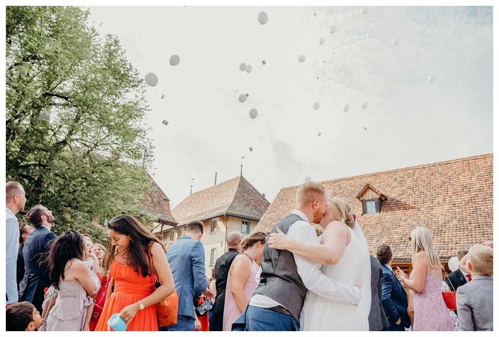 bride and groom kiss as balloons fly in the air at the Kulturhof Schloss Köniz wedding reception in Bern Switzerland
