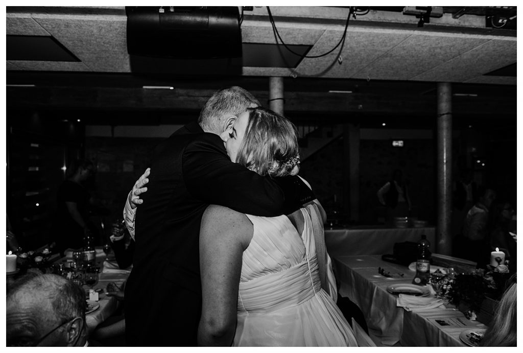 black and white photo of the bride and her father hugging during their koniz castle wedding reception in bern Switzerland