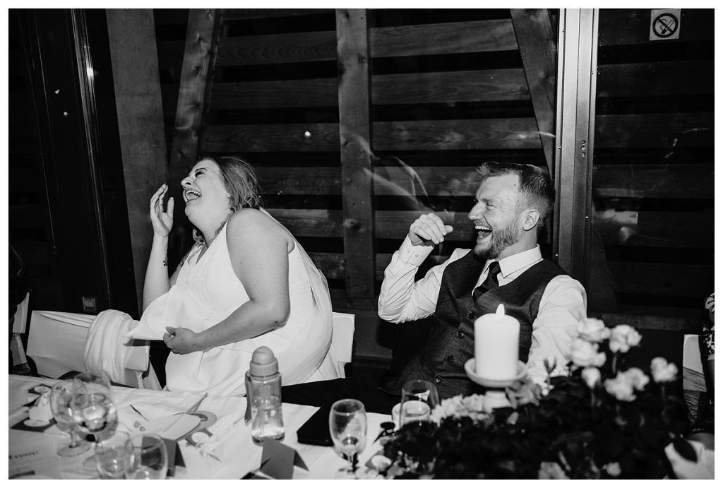 black and white photo of bride and groom laughing while sitting at their table during their koniz castle wedding reception