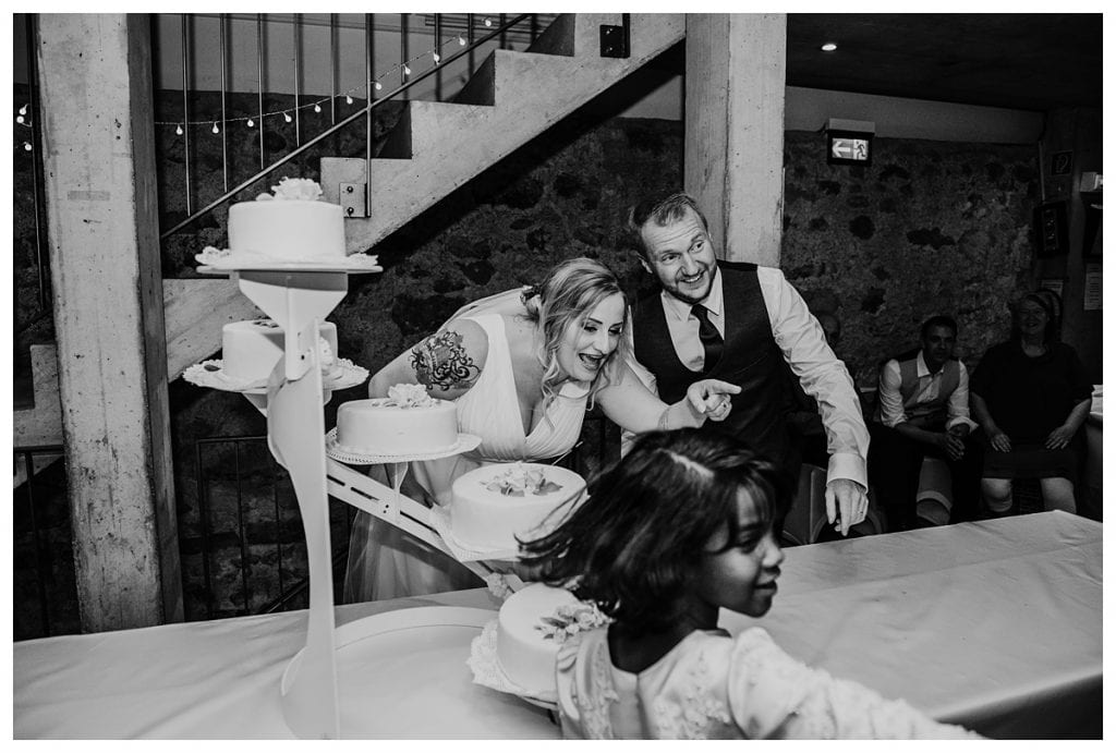 bride pointing to young girl as they cut their wedding cake at their castle koniz wedding reception in bern Switzerland