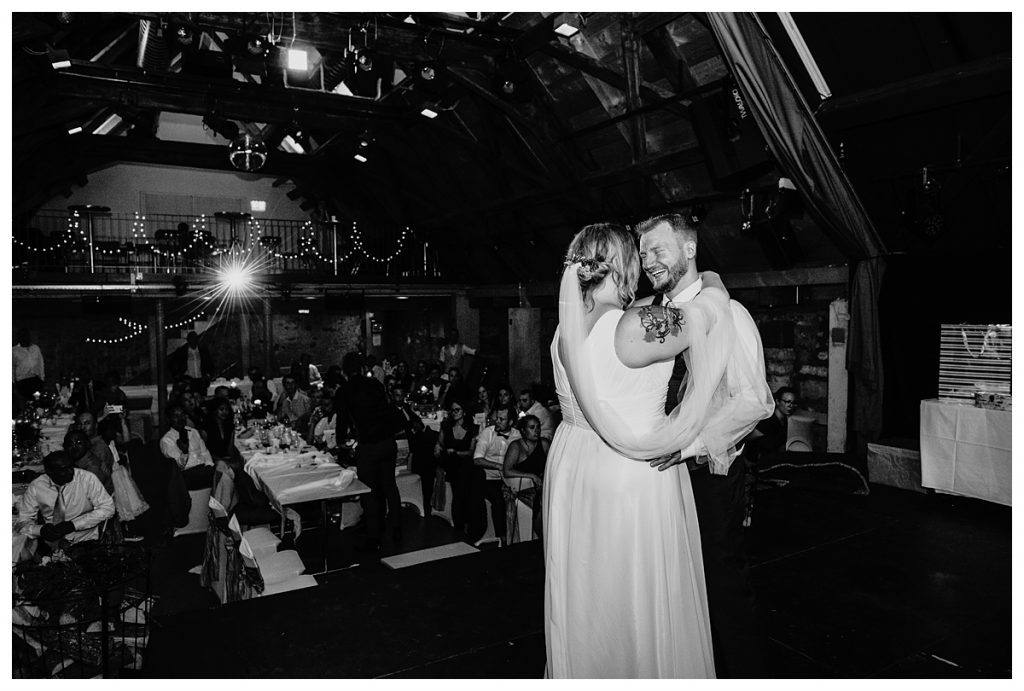 black and white photo of bride and groom having their first dance during their castle koniz wedding reception in bern Switzerland