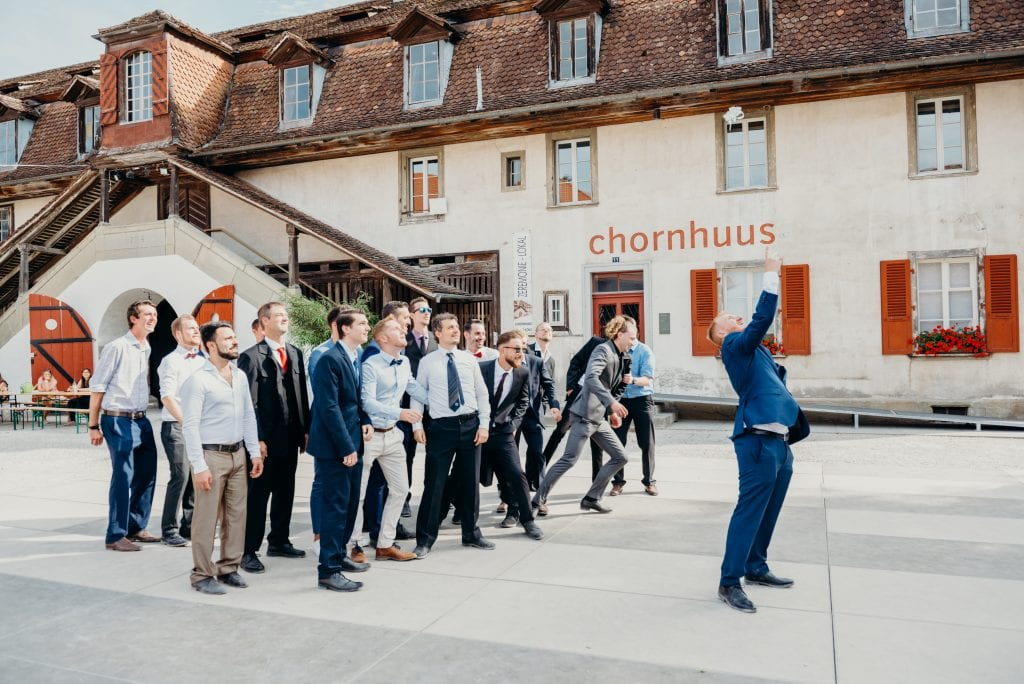 garter in mid air as groom leans back and men try to catch it at Kulturhof Schloss Köniz in bern Switzerland
