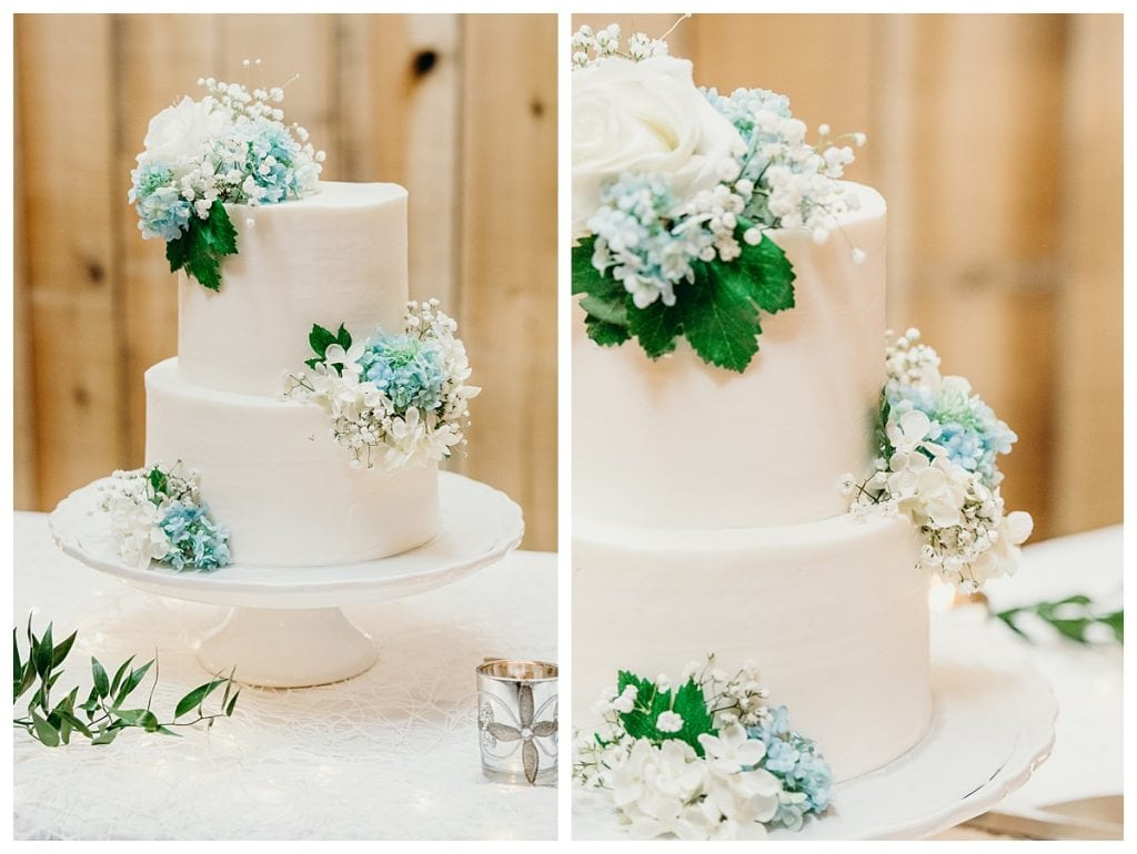 megalicious white wedding cake with blue flowers on display at Firefly Lane weddings