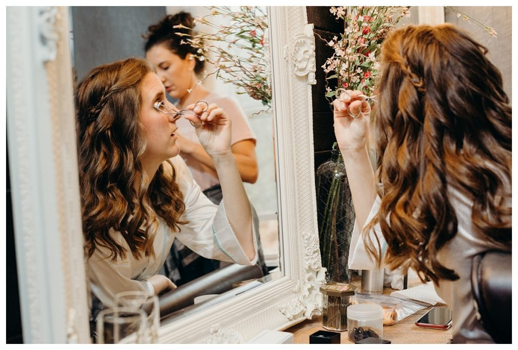 Bride curling her eyelashes before her Tennessee wedding at Firefly Lane.