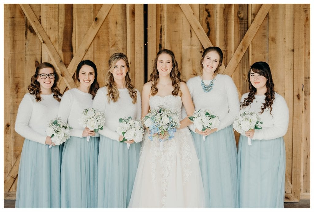 bride and bridesmaids in blue skirts with their bouquets against Firefly Lane's barn door