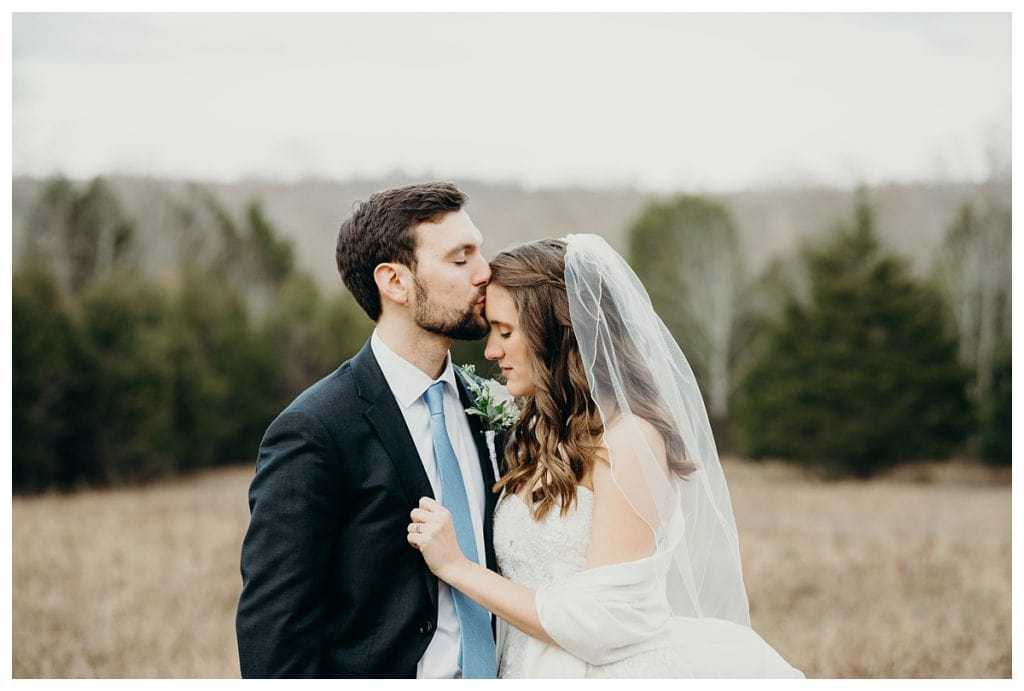 groom kissing bride's forehead in the woods at Firefly Lane wedding venue