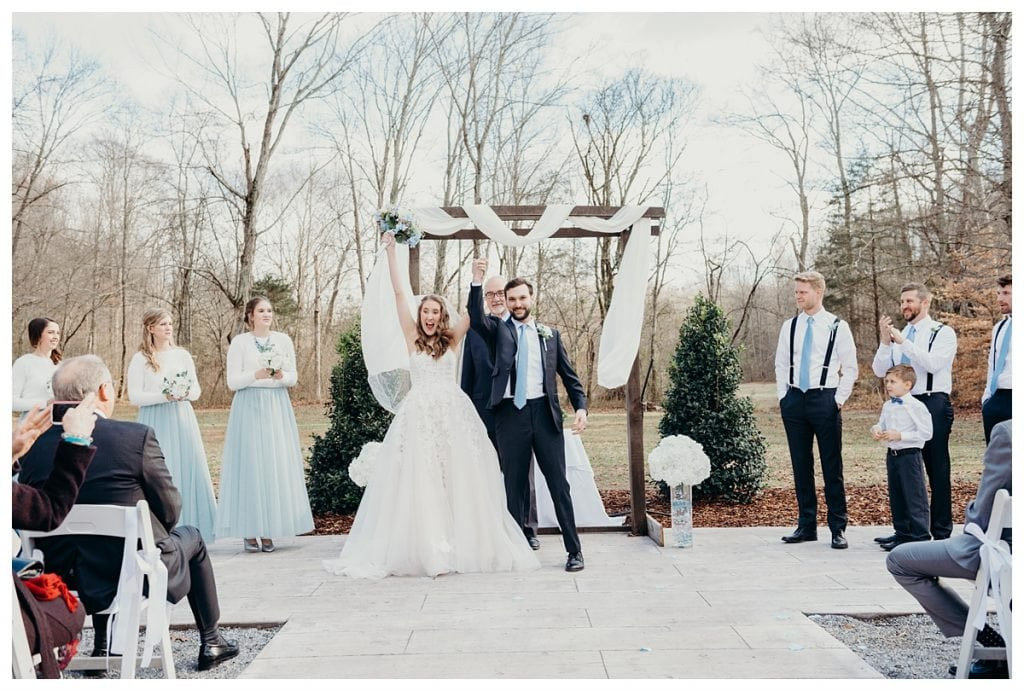bride and groom cheer raising arms after Firefly Lane wedding ceremony