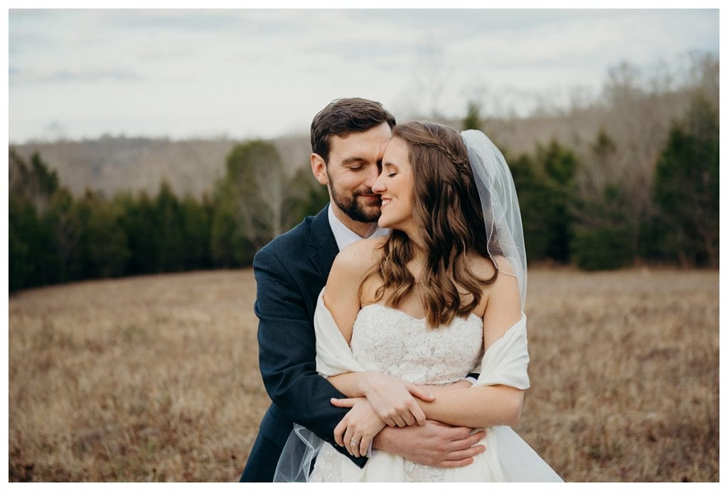 couple's heads touching during formal wedding portraits in a field at Firefly Lane