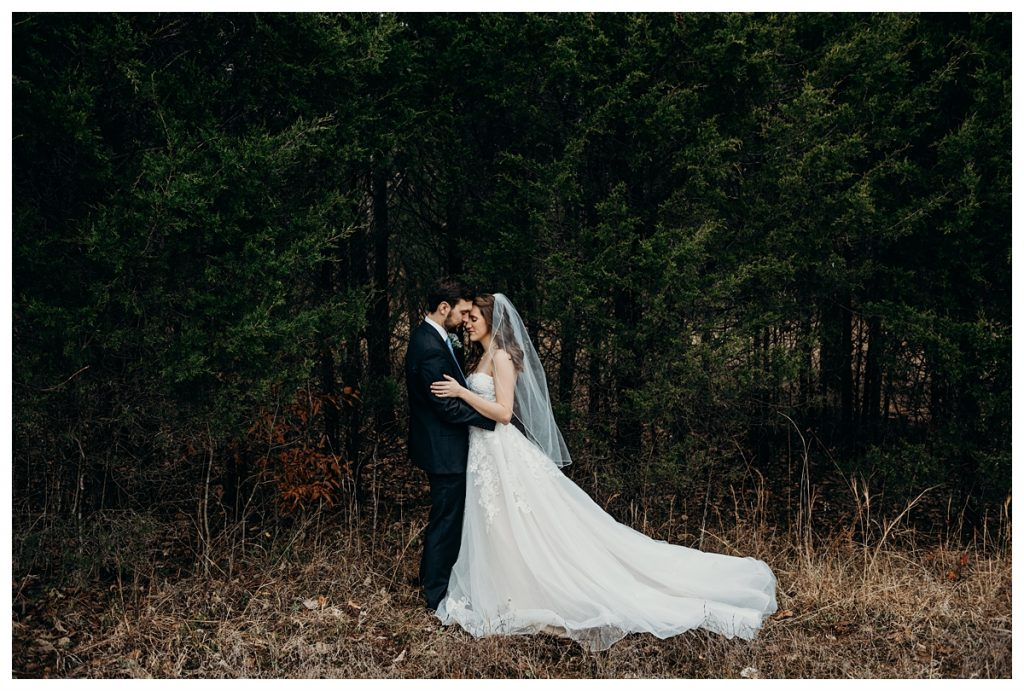 bride and groom touching heads during their formal portrait session in the woods at Firefly Lane